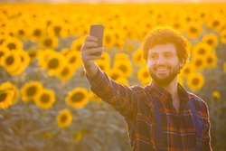 Handsome young farmer standing in the middle of a golden sunflower field smiling and taking a selfie with his phone during a majestic sunrise.