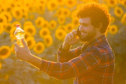 Handsome young farmer standing in the middle of a golden sunflower field smiling and talking on phone while holding up a sunflower oil bottle during a majestic sunrise.