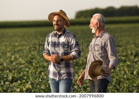 Handsome young farmer wearing straw hat laughing. Senior farmer holding straw hat in hand talking smiling.