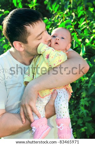 Handsome young father kissing his little baby on green tree background