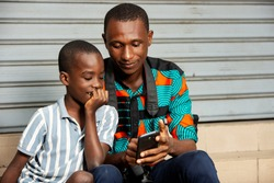 handsome young father sitting with his son, father showing images to his son on mobile phone in the street while smiling