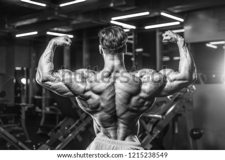 Handsome young fit muscular caucasian man of model appearance workout training in the gym gaining weight pumping up muscle, poses, drinks water  fitness and bodybuilding sport nutrition concept