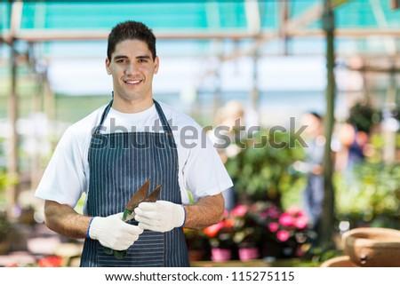 handsome young gardener portrait in greenhouse