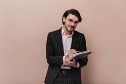 Handsome young gentleman with brunette hair, white shirt, black striped suit smiling, writing something in notebook and looking into camera. Man posing isolated over beige background