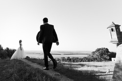 Handsome young groom walking to beautiful stylish bride in the field with sky background b&w