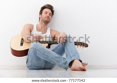 Handsome young guitarist listening to music through headphones eyes closed.?