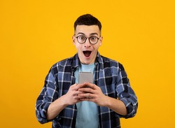 Handsome young guy in glasses looking at his smartphone in shock on orange studio background. Surprised millennial man with mobile phone amazed at promo sale or huge discount