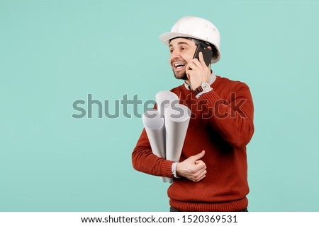 Handsome young handsome bearded engineer or constructor man in casual outfit speak on smartphone over cyan background. Architecture and Renovation concept.