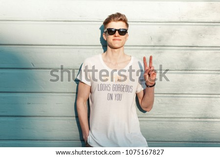 Handsome young happy man hipster with a smile with fashionable sunglasses shows a peace sign near a wooden blue wall on the beach #1075167827