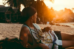 Handsome young hipster man enjoy the sunset on the beach,relaxing smoking and drinking bottle bear,freedom concept of hiker man,Los-Angeles,California beach coast,travel bag,mans fashion store,summer