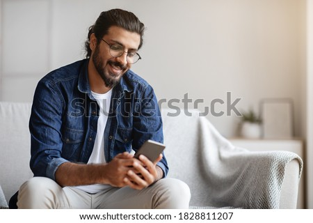 Handsome young indian guy sitting with smartphone in hands at home, messaging with friends, relaxing with cellphone on sofa, checking new app, enjoying mobile communication or browsing social networks
