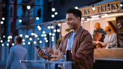 Handsome Young Indian Man is Using a Smartphone while Sitting at a Table in a Outdoors Street Food Cafe. He's Browsing the Internet or Social Media, Posting a Status Update. Man is Happy and Smiling.