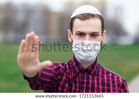 Handsome young Jewish guy in traditional jewish male headdress, hat, boom, or yiddish on head. Man in medical mask on his face showing palm, stop sign against coronavirus, virus pandemic. Covid-19 Foto stock ©