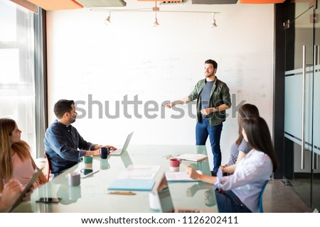 Handsome young latin businessman giving a presentation to a group of people in a meeting room