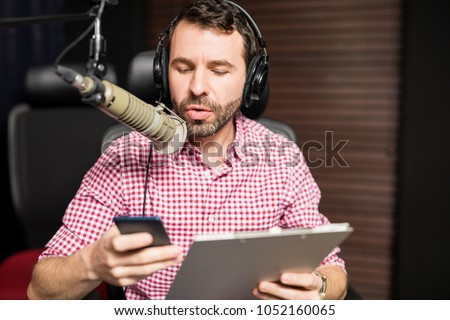 Handsome young latin man working as radio host at radio station sitting in front of microphone holding clipboard and using mobile phone