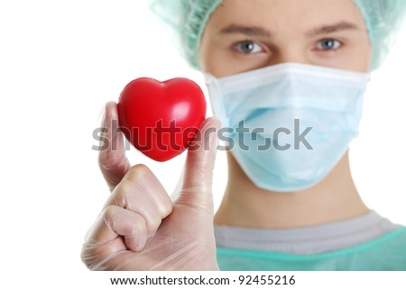 Handsome young male doctor holding heart shape toy, on white