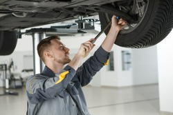 Handsome young male mechanic inspecting undercarriage of a car using a wrench profession job occupation safety automotive transport vehicle business tools instruments garage repair shop service
