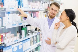 Handsome young male pharmacist woking with his client advicing mature Asian woman something from a shelf at his drugstore assistance help consultation doctor prescription salesperson clinician