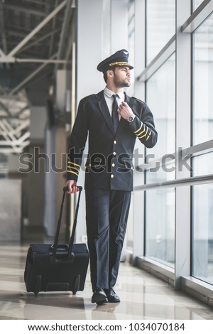 Handsome young male pilot is walking in the airport terminal.