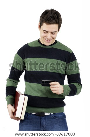 Handsome young male student laughing carrying books and checking his text message on his cell phone - stock photo