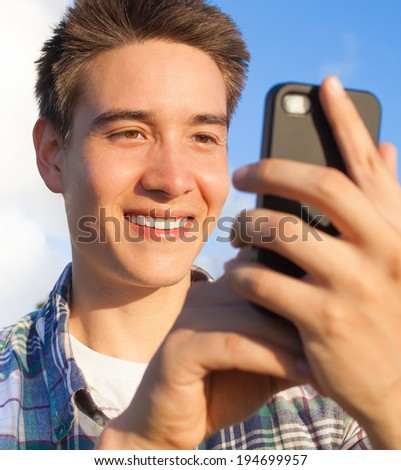 Handsome young male using cellphone mobile phone.