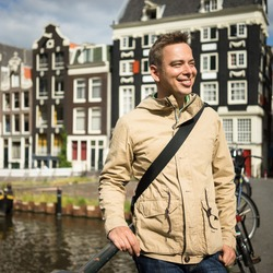 Handsome young man, admiring the beauty of Amsterdam center on a bridge in a sunny summer day