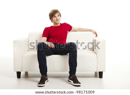 Handsome young man at home sitting on the couch