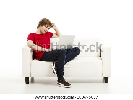 Handsome young man at home sitting on the couch and working on the laptop