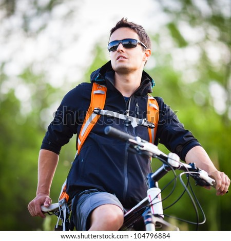 Handsome young man biking in the countryside - stock photo
