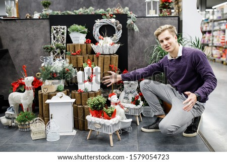 Handsome young man chooses holiday decor for the New Year holidays. Holidays #1579054723