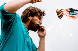 Handsome young Man dancing and playing mouth organ outdoors against the grey sky.Bohemian Man playing folk American music on Harmonica Instrument