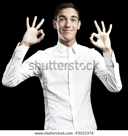 Handsome young man doing the ok sign over black background
