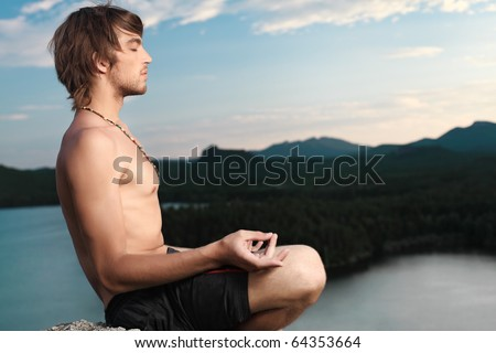 Handsome young man doing yoga exercise outdoors.