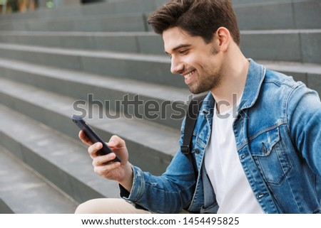 Handsome young man dressed casually spending time outdoors at the city, sitting on stairs