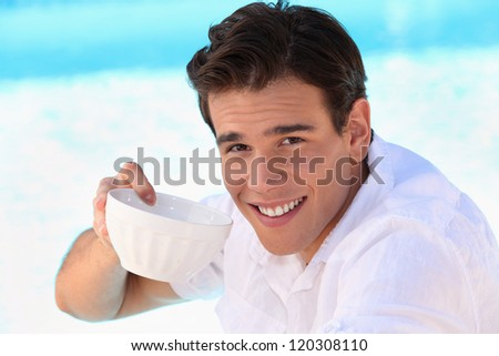 Handsome young man drinking from a bowl