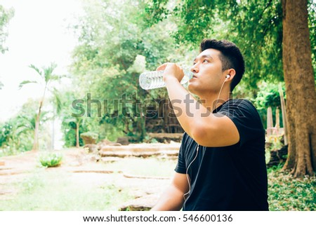 Handsome Young man drinking water from a bottle After Training. #546600136