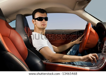 Handsome young man driving modern sport car