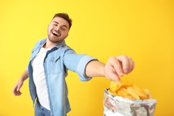 Handsome young man eating tasty potato chips on color background