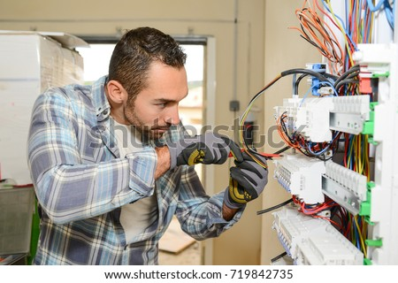 handsome young man electrician working on switchboard of house building construction site