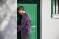 Handsome young man entering home through a green door in an exterior wall of a house