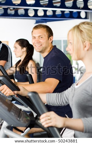 Handsome young man exercising in the gym with group of friends