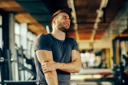 Handsome young man feeling the pain in hand at the gym