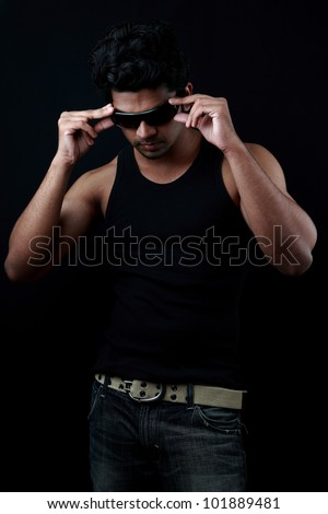 Handsome young man fixes his sunglasses in a dark background