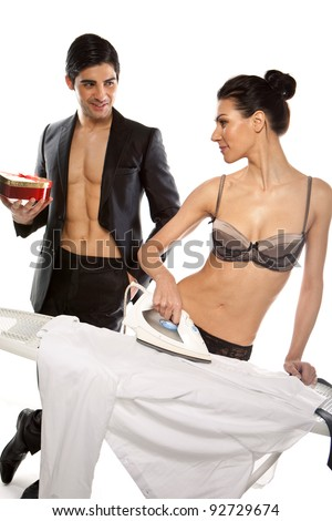 Handsome young, man giving a gift to a gorgeous woman in lingerie who is ironing his shirt