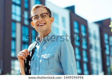 Handsome young man. Handsome young man wearing striped shirt feeling excited while going to the office