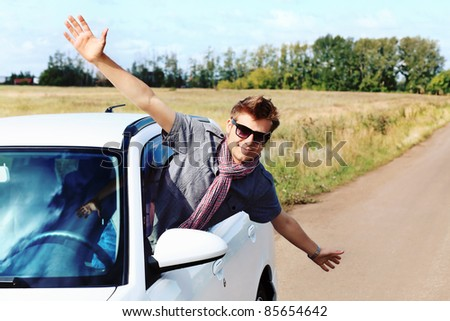 Handsome young man having summer trip on a car.