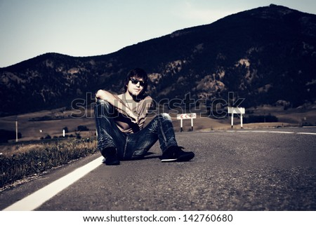 Handsome young man hitchhiker sitting on a road over picturesque landscape.