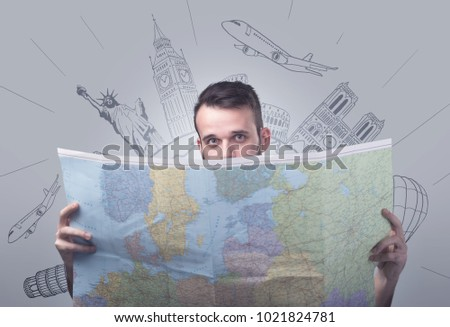 Handsome young man holding a map with famous sightseeing destinations above his head #1021824781