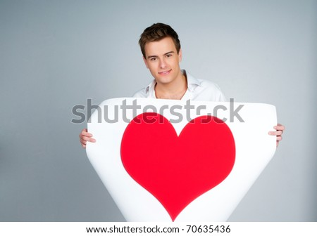 handsome young man holding a red heart