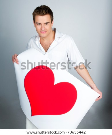 handsome young man holding a red heart - stock photo